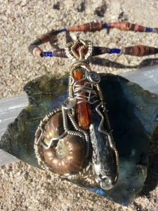 "CH021813.P.79 Blue Kyanite, Orange Kyanite, and Ammonite Pendant in Sterling Silver & Gold  Chakras: Third Eye, Throat, Sacral, Root  Size: 2 3/4 "" x 1 1/4 "" x 3/4″  Kyanite is one of the few minerals in the mineral kingdom that never needs cleaning or cleansing. It will NOT accumulate or retain negative energy or vibrations. The energy of Kyanite in unlimited in application, making it one of the very best attunement stones. Kyanite aligns all chakras automatically and immediately, with no conscious direction. If directed with the consciousness of the user, it can also open the chakras. Conscious direction of the energy can also align the emotional, intellectual, physical, spiritual, ethereal, astral bodies. It brings tranquillity and calming effect to the whole being. Kyanite facilitates meditation. It balances the yin/yang energies. Assists in opening the Third eye for clear vision. Blue kyanite is also good for protection against outside negative energies. The orange kyanite will activate and nourish the sexual energy center, similar to other orange stones, such as carnelian, for example.  Ammonite aids in seeing 'the whole picture'. A protective stone used to create stability and structure in your life. Transforms the negative energies in your life into a positive flow. Aids in relaxation especially in the birthing process. Good for treatment of lungs and limbs."